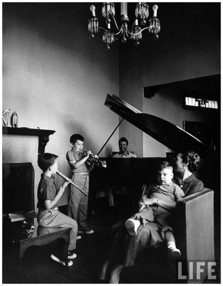 Dave Brubeck, at piano, children playing instruments, wife holding baby in Los Angeles apartment