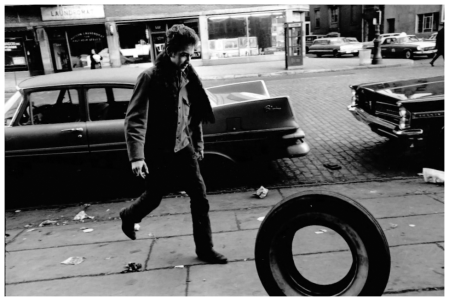 Bob Dylan – Photo Jim Marshall photograph of Bob Dylan rolling a tire down a Greenwich Village street in 1963