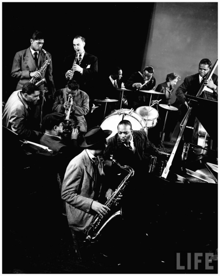 Count Basie at piano, Lester Young on sax seated next to him & wearing hat, with Dizzy Gellespie behind him, Mezz Mezzrow on clarinet & other unident. musicians during jam session at Gjon Mili's studio 1943