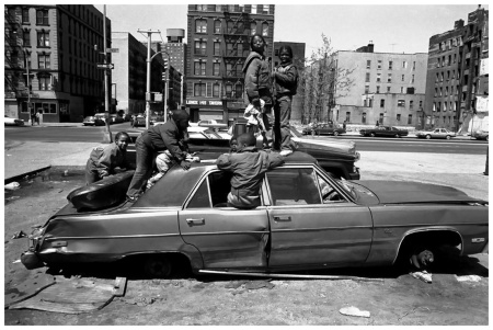 Eli Reed USA. New York City. 1987. Harlem street scene. Child playing in an unfed car