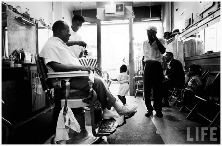Musician Louis Armstrong (L) in his neighborhood barber shop Queens, NY, US 1965 John Loengard