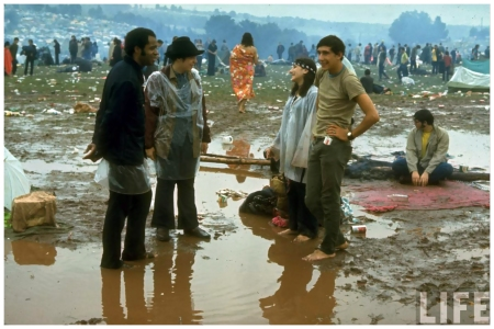 Photo John Dominis Young people standing in the mud & water talking, during the Woodstock Music & Art Fair 1969