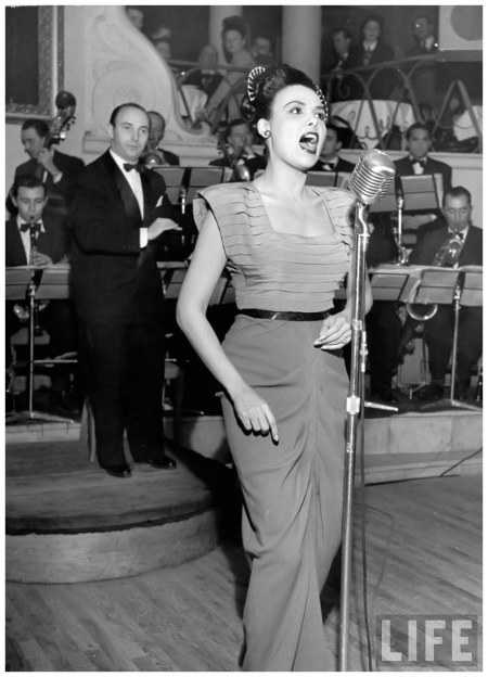 Singer Lena Horne singing into mike on stage as they bandleader conducts an orchestra behind her in nightclub