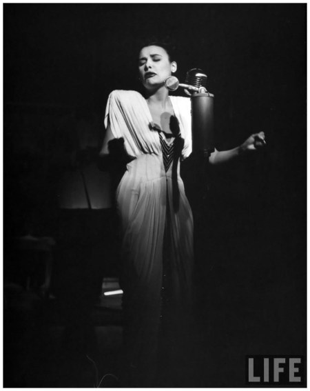Singer Lena Horne singing into mike on stage in nightclub 1947