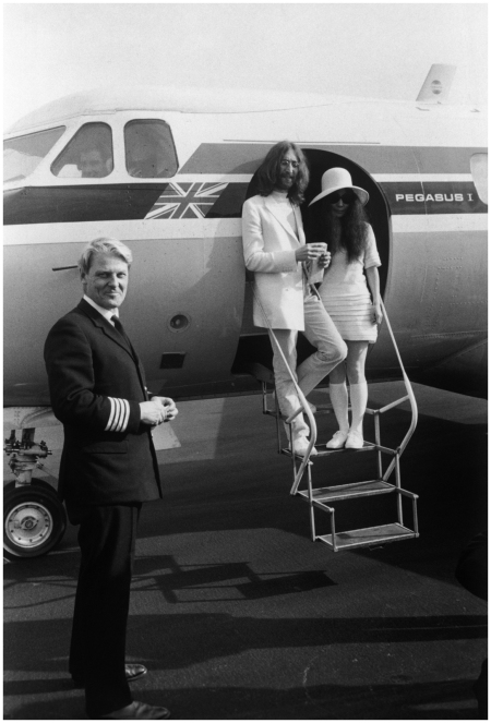 John Lennon and Yoko Ono, both dressed in white, board a private aircraft in Gibraltar after their wedding, 20th March-1969
